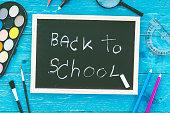 Back to School chalkboard  with school supplies on wooden backgr