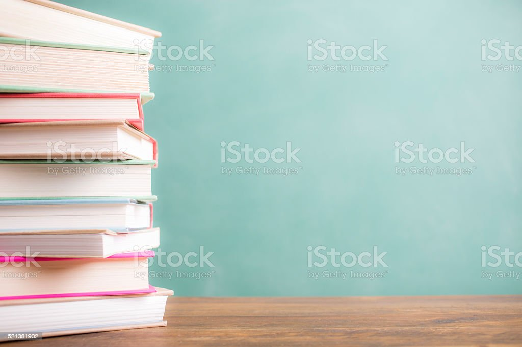 Back to school. Education. Textbooks stacked on desk. Chalkboard. stock photo