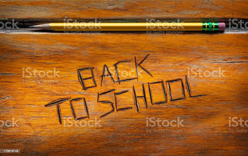 'Back to School' etched into old wooden desktop stock photo