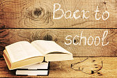 Back to school inscription with books over an rustic table