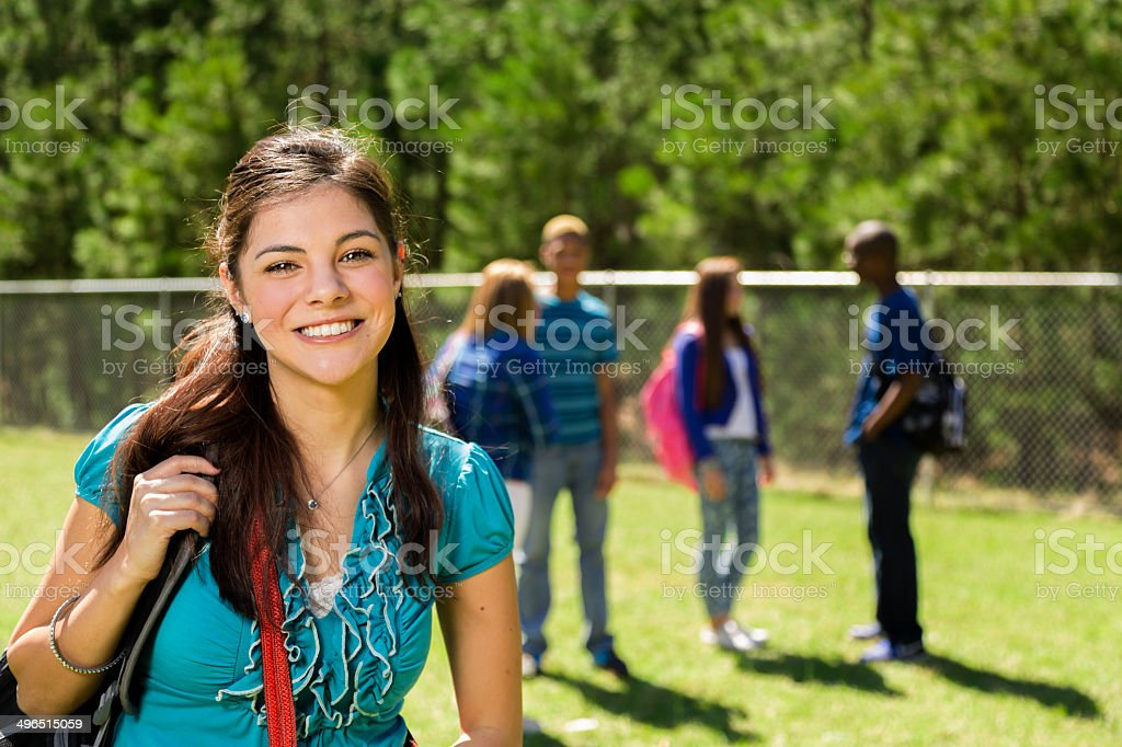 Back to School: Latin girl on school campus. Friends background. stock photo