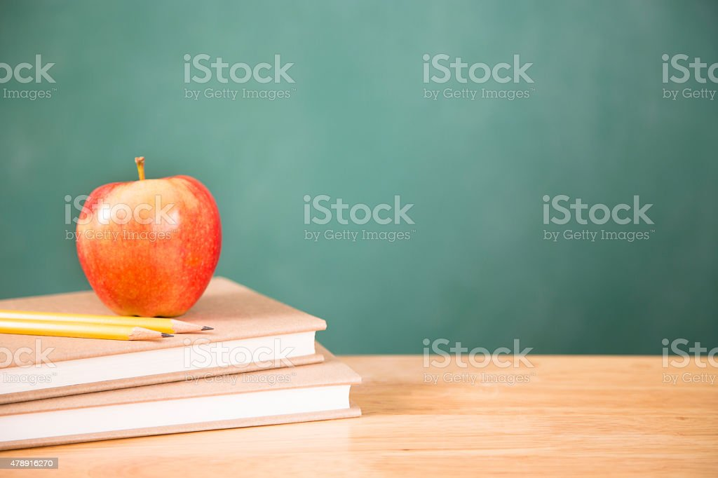 Back to school. Textbooks, apple, pencils on desk. Chalkboard. stock photo