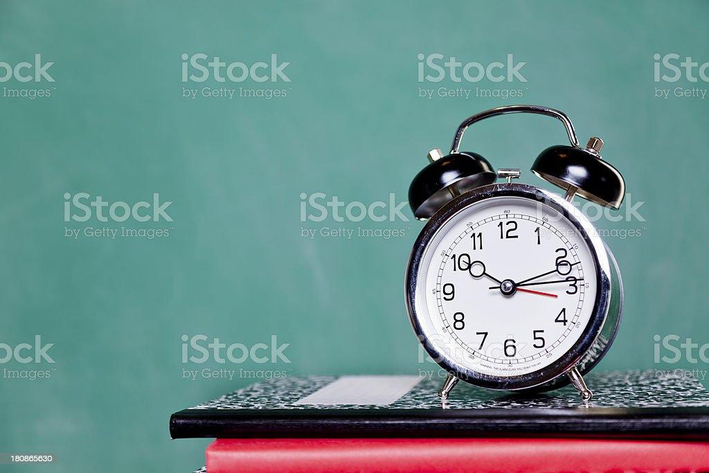 Back to School time:  Alarm clock on books.  Chalkboard.  Education. stock photo
