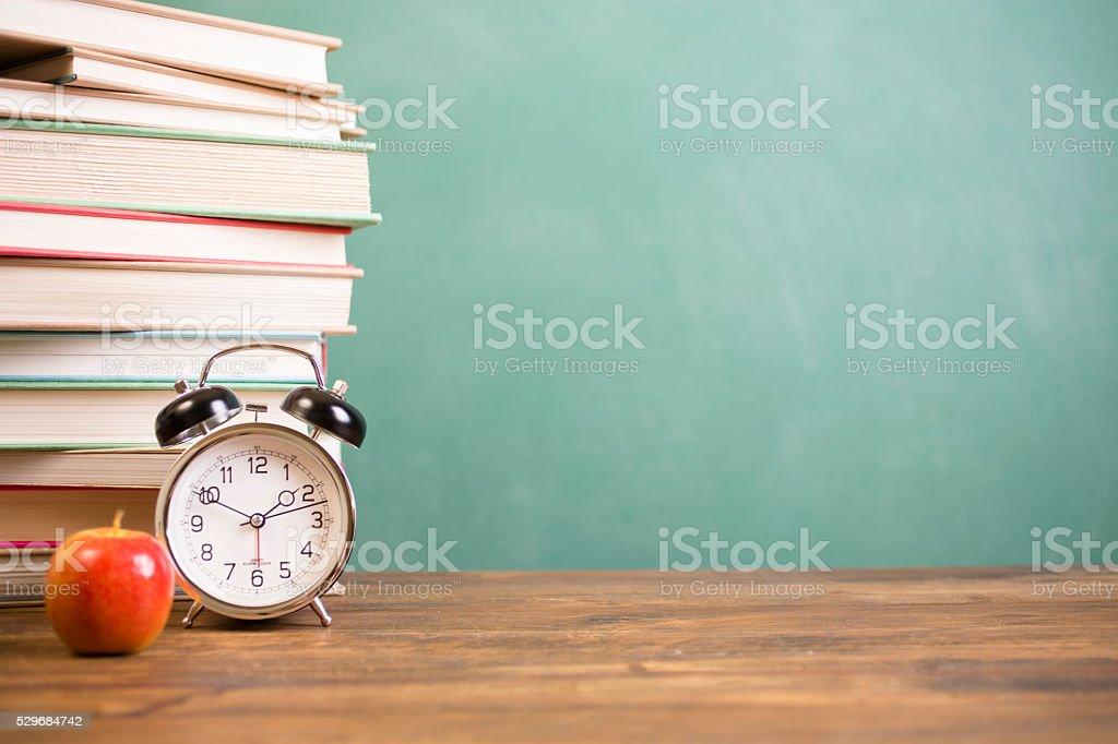 Back to school time. Education. Textbooks, alarm clock, chalkboard. stock photo
