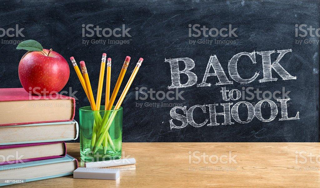 back to school - written on blackboard with book stock photo