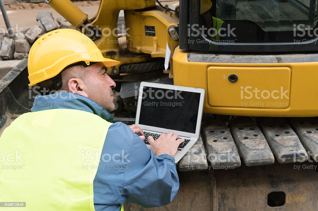 Back turned engineer at work with tablet computer. Outdoors stock photo