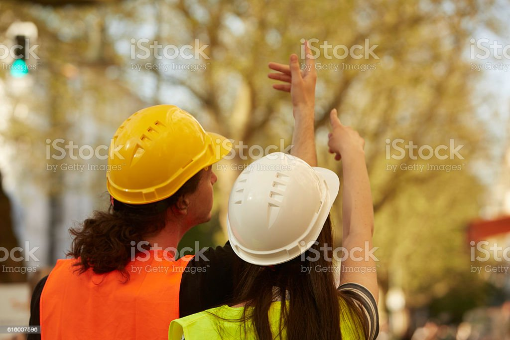 Back turned engineers with safety workwear pointing at something stock photo
