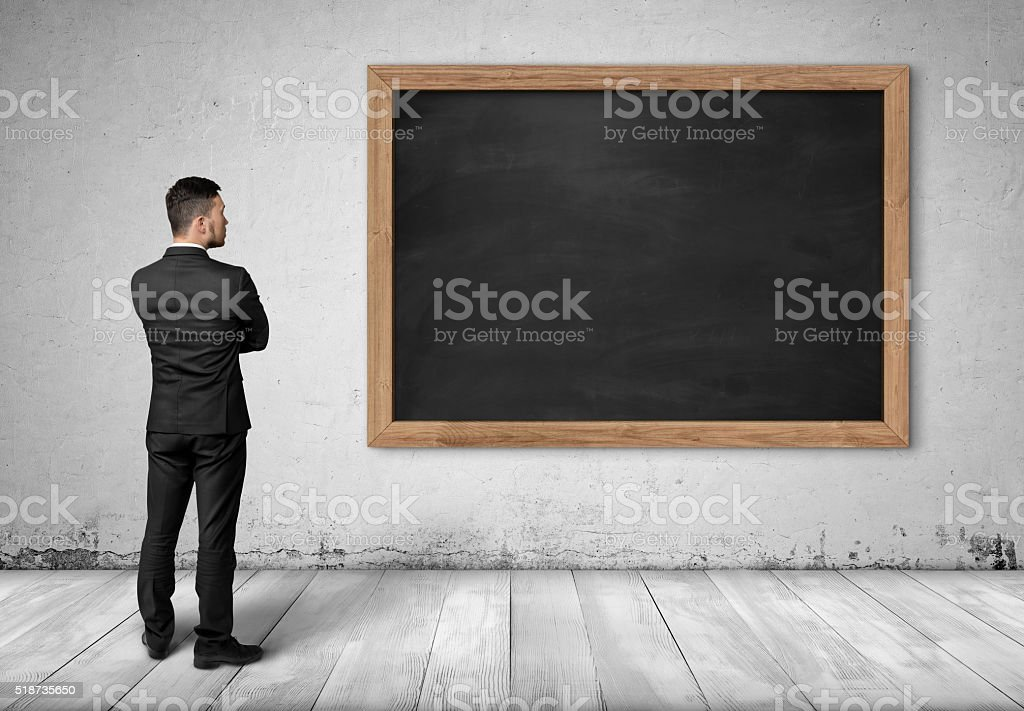 Back view businessman full body standing front of black chalkboard stock photo
