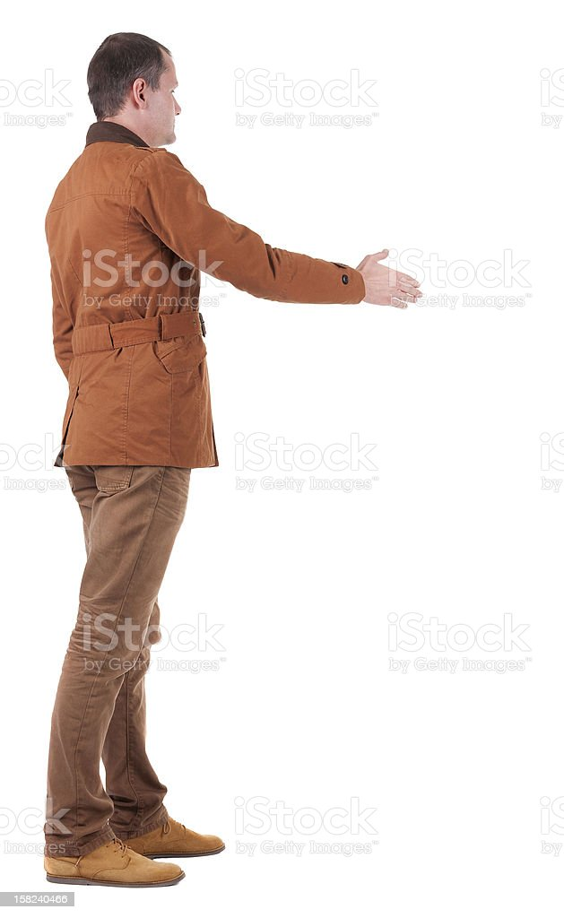 back view businessman in  movement reaches out to shake hands royalty-free stock photo