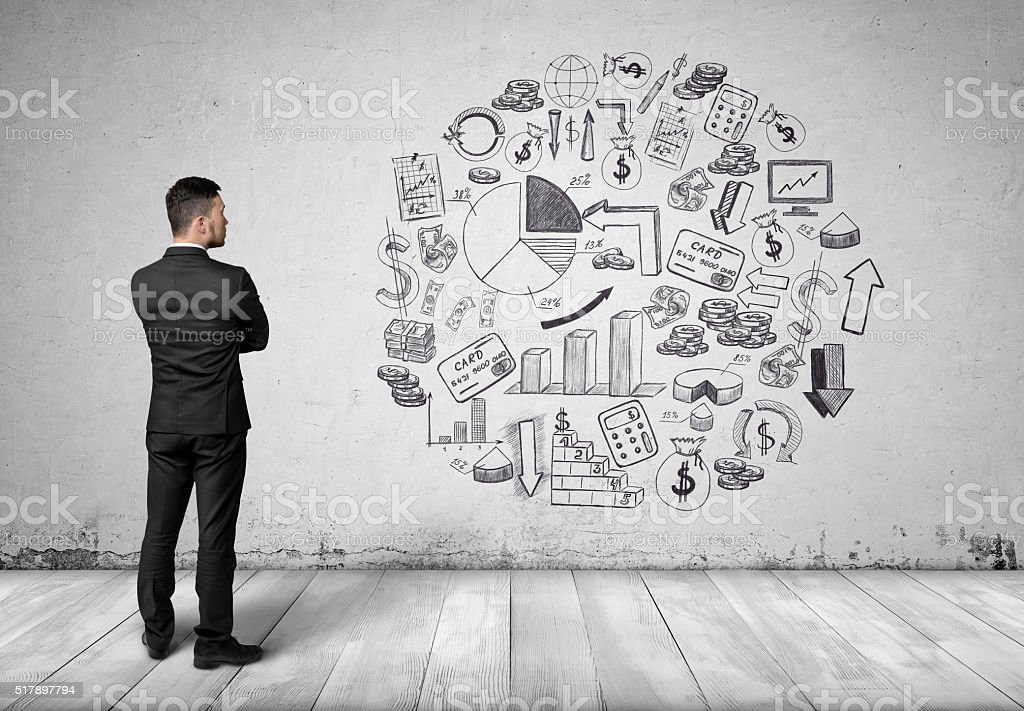 Back view businessman looking at white wall with business sketches stock photo