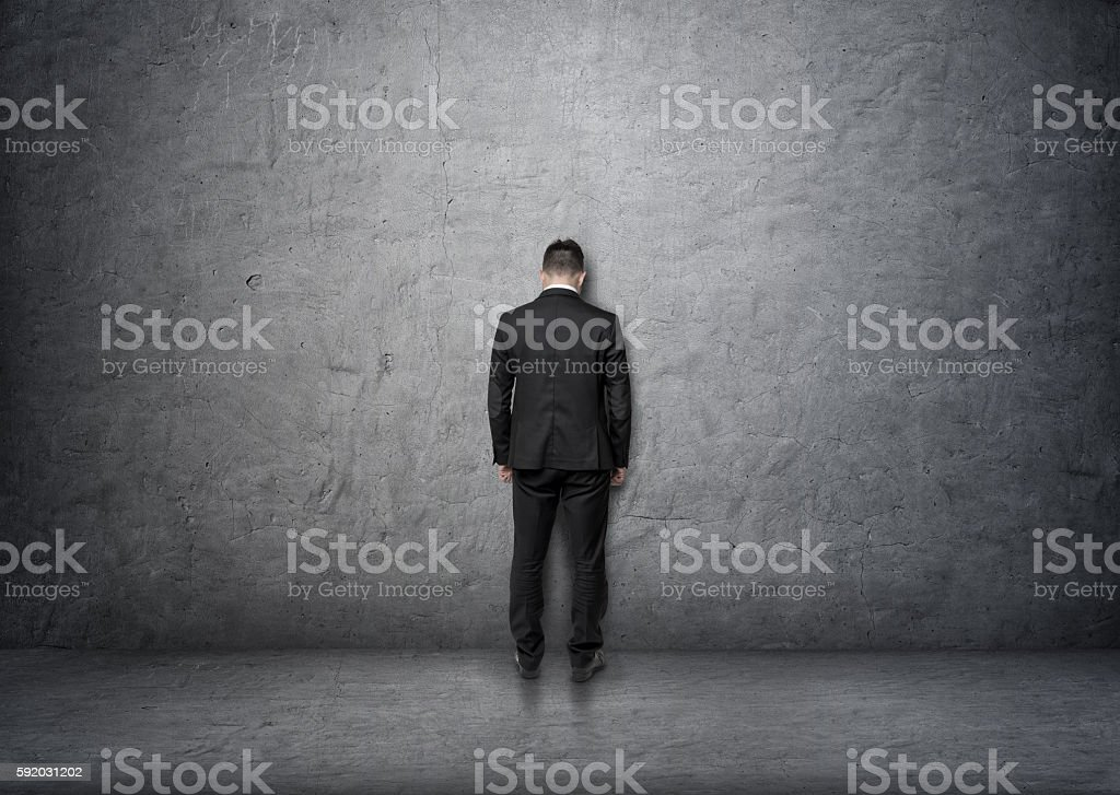 Back view businessman with bowed head standing in front of stock photo