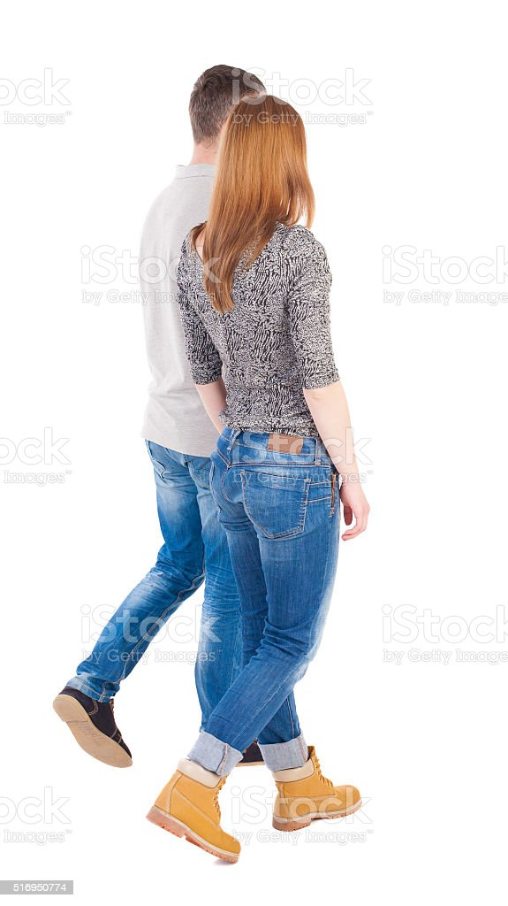 Back view going couple. walking friendly girl and guy holding stock photo