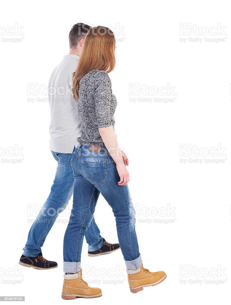 Back view going couple. walking friendly girl and guy stock photo