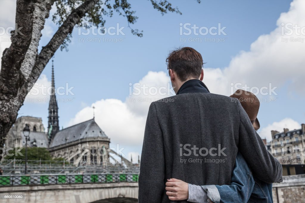 back view happy quirky Caucasian and oriental multiracial couple by river Seine near Notre Dame in Paris stock photo