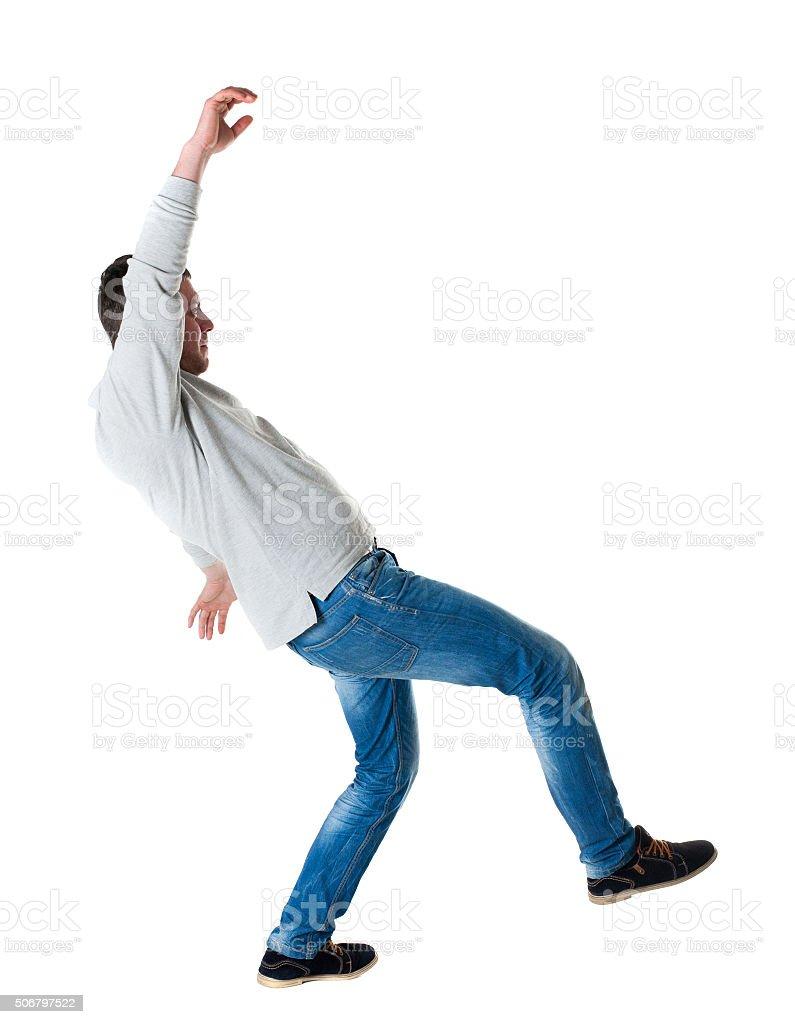 Back view man Balances waving his arms. stock photo