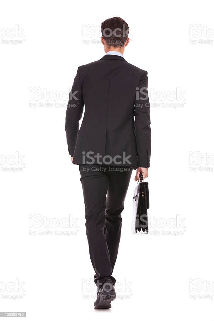 back view of a business man holding briefcase and walking stock photo