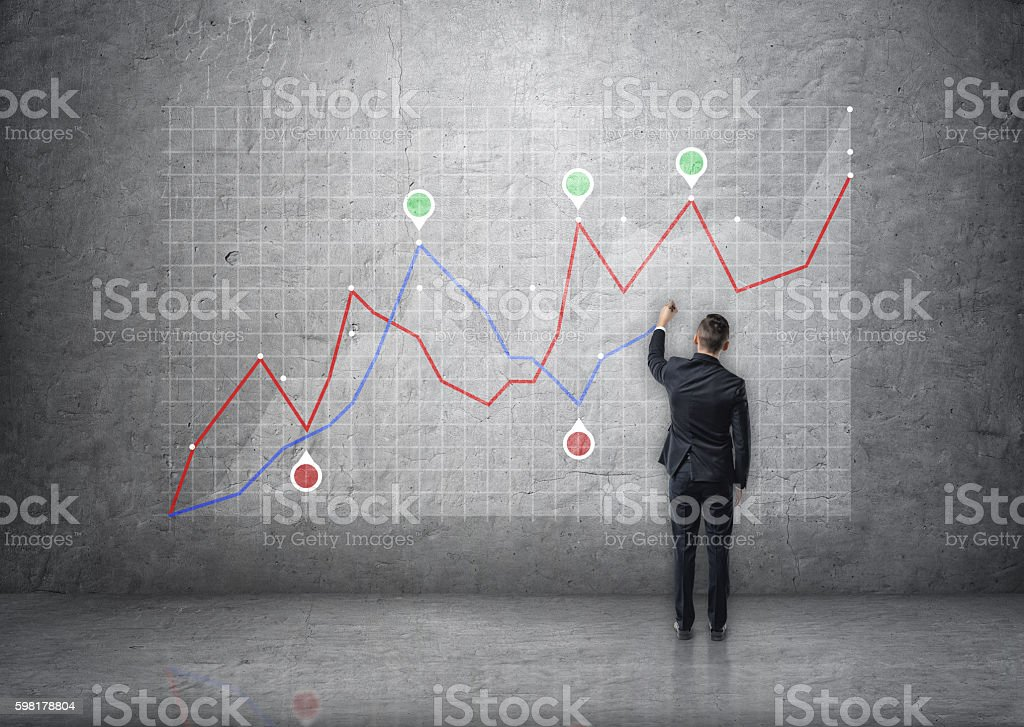 Back view of a businessman drawing rising graph on concrete stock photo
