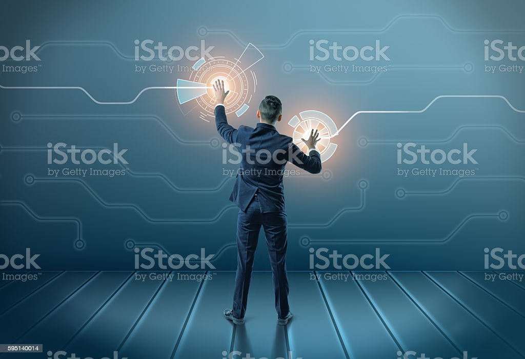 Back view of a businessman touching icons on digital screen stock photo