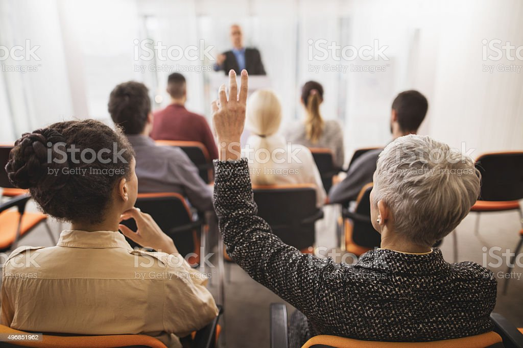 Back view of a businesswoman asking a question on seminar. stock photo