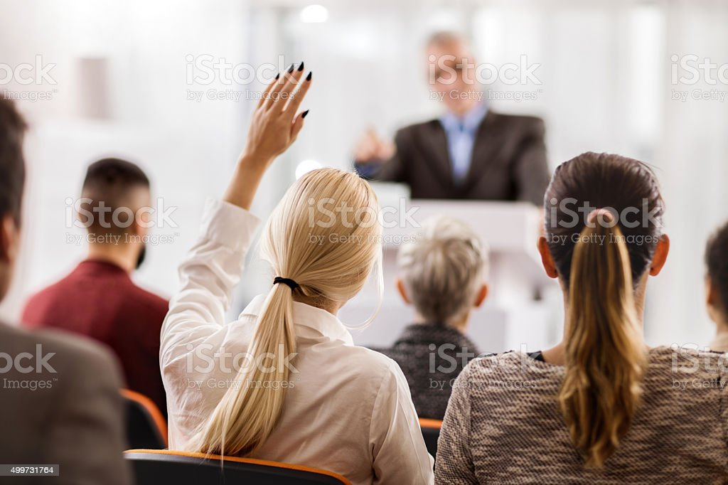 Back view of a businesswoman asking a question. stock photo
