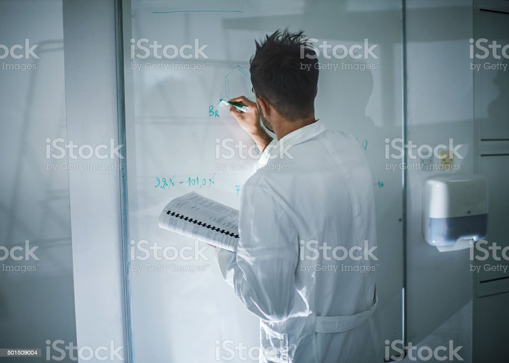 Back view of a chemist writing formula on whiteboard. stock photo