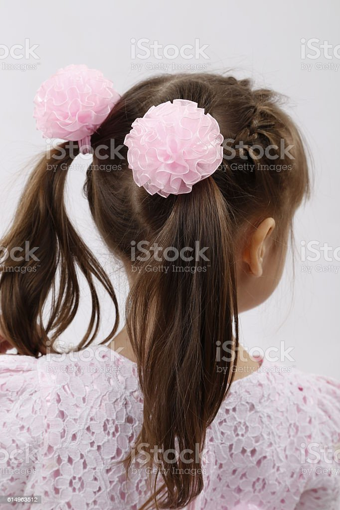 Back view of a little girl hairstyle with pink bow-knots stock photo