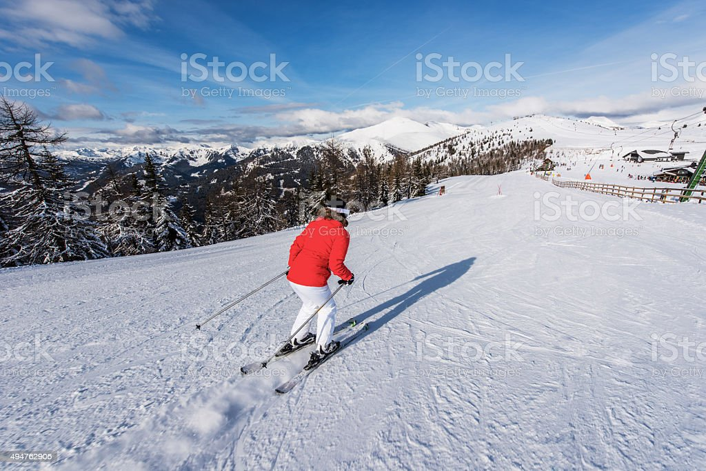Back view of a skier moving down the ski slope. stock photo