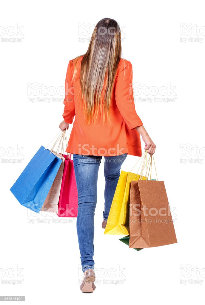 back view of a woman jumping with shopping bags. stock photo