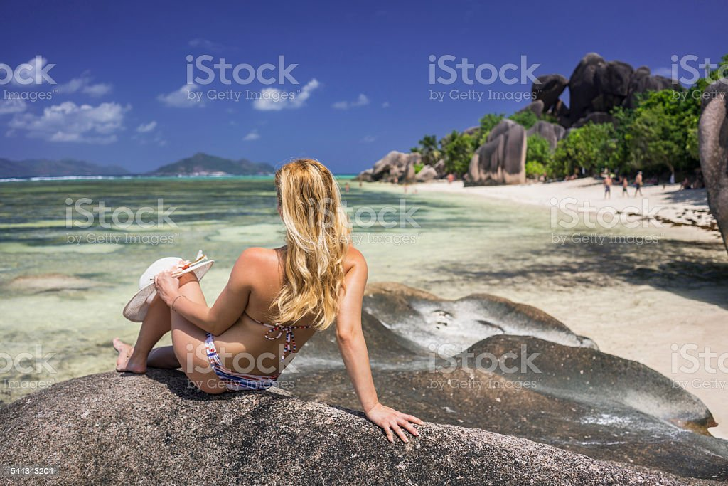 Back view of a woman on the rock at beach. stock photo