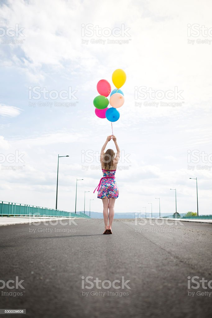 Back view of a woman with group of multi-colored balloons. stock photo