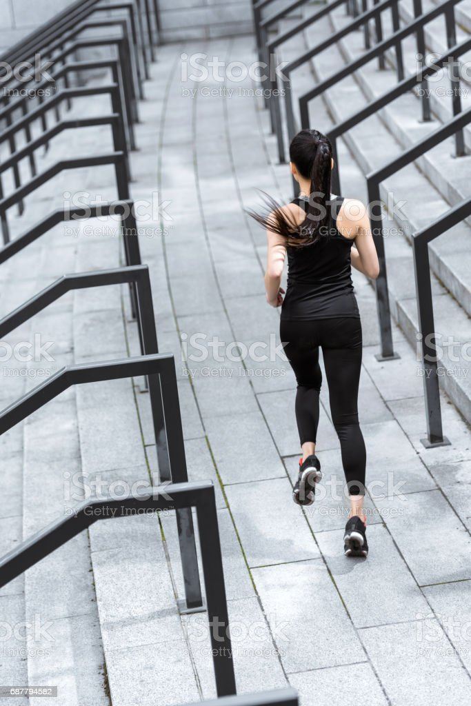 Back view of athletic young woman in sportswear running on stadium stairs stock photo