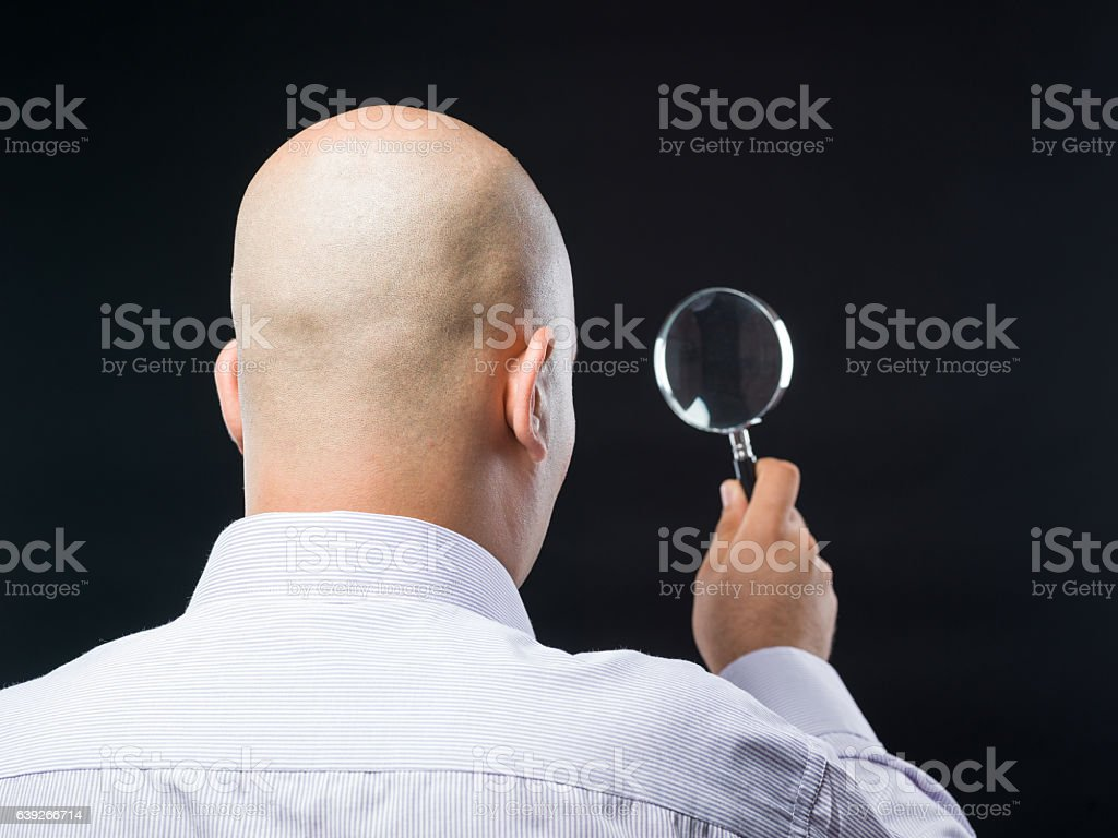 Back View Of Bald Headed Man Holding Magnifying Glass stock photo