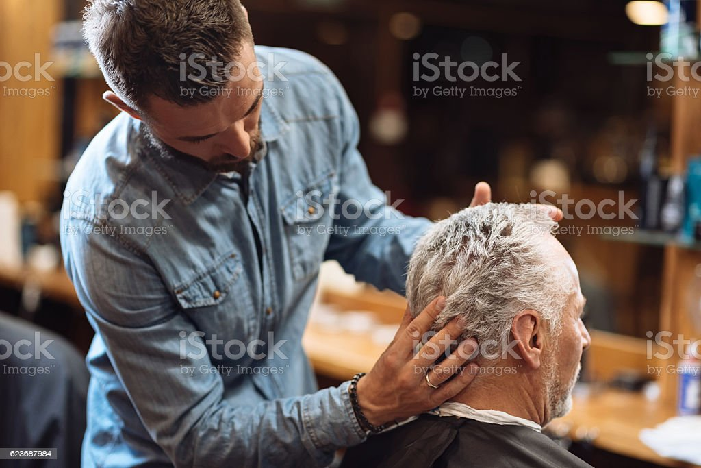 Back view of barber styling seniors client hair stock photo