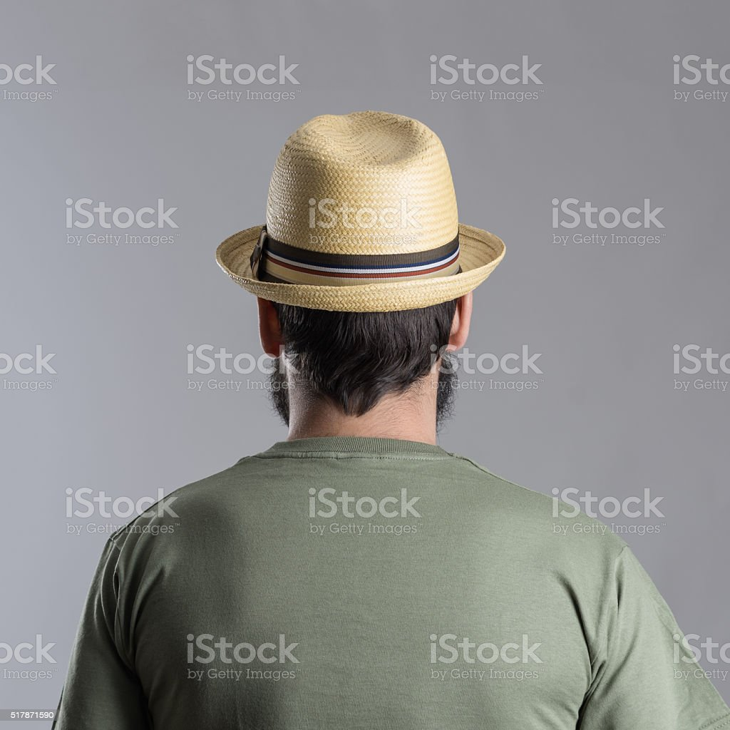Back view of bearded man with straw hat looking away. stock photo