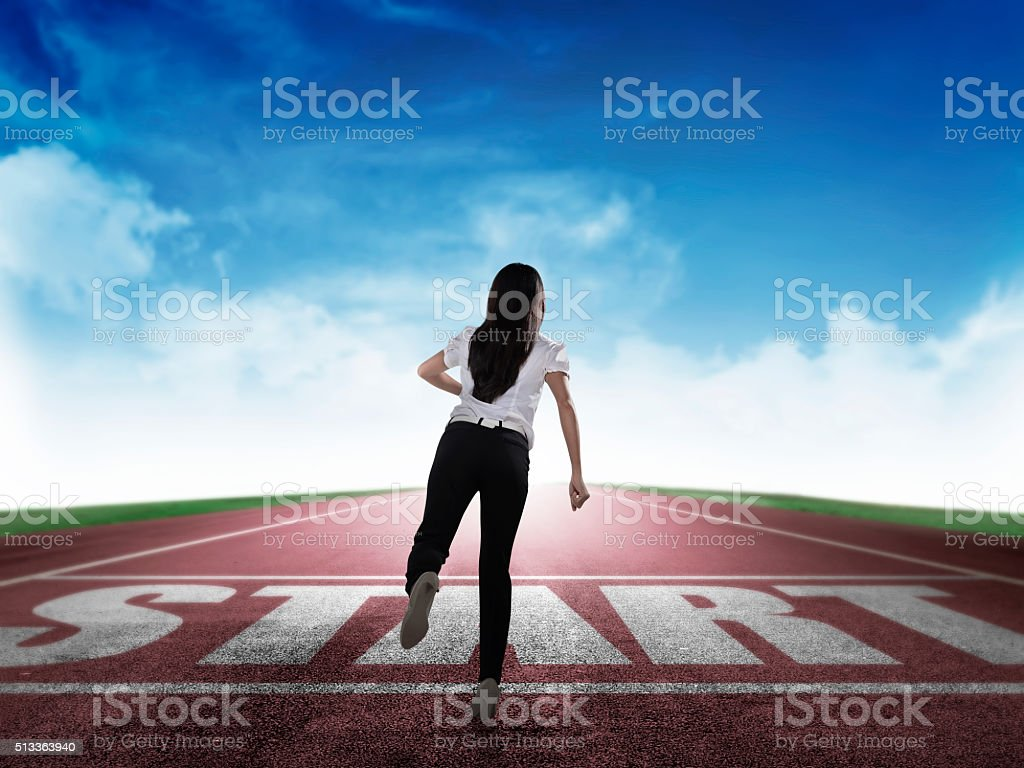 Back view of business woman running from start line stock photo