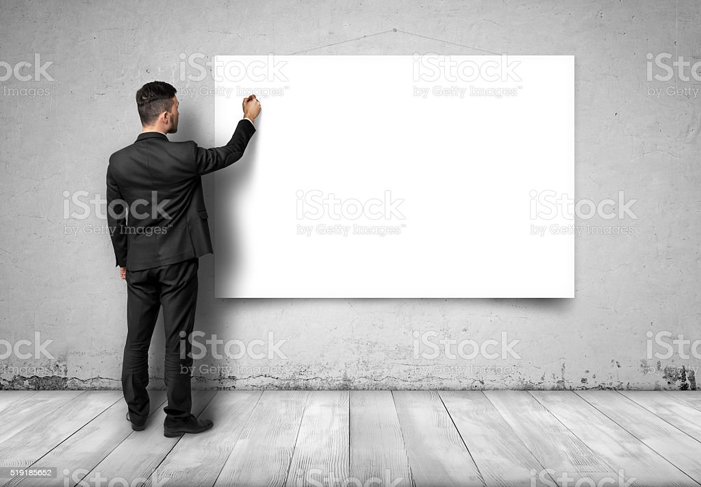 Back view of businessman drawing at white empty canvas on stock photo
