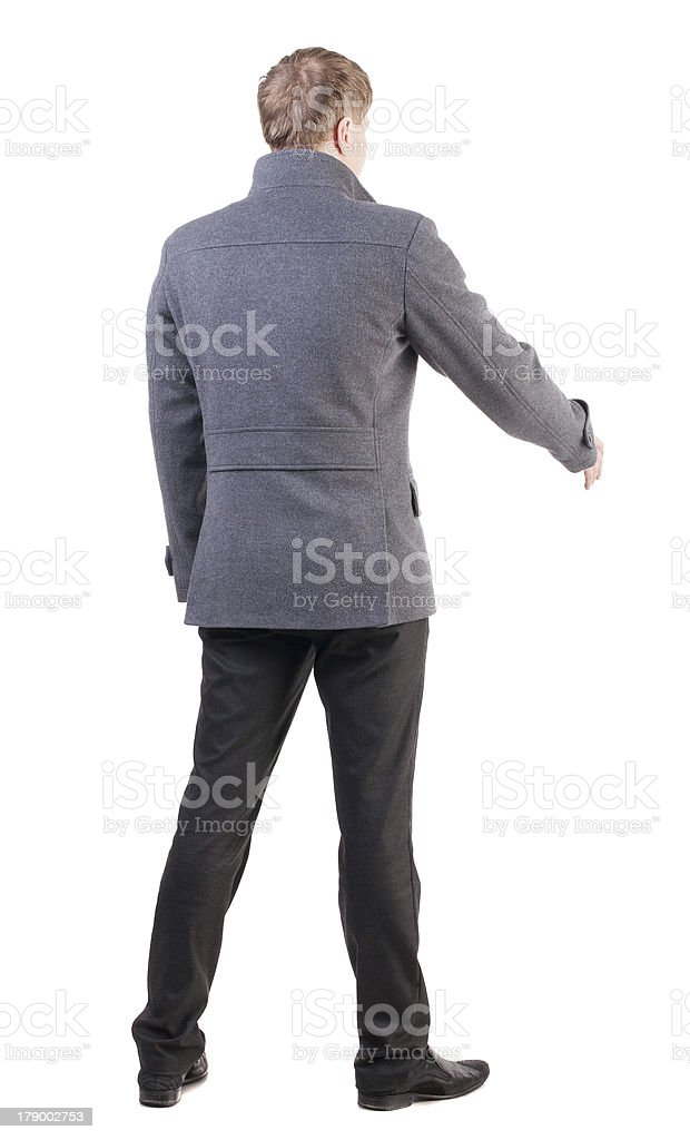 back view of businessman in coat reaches to shake hands. royalty-free stock photo