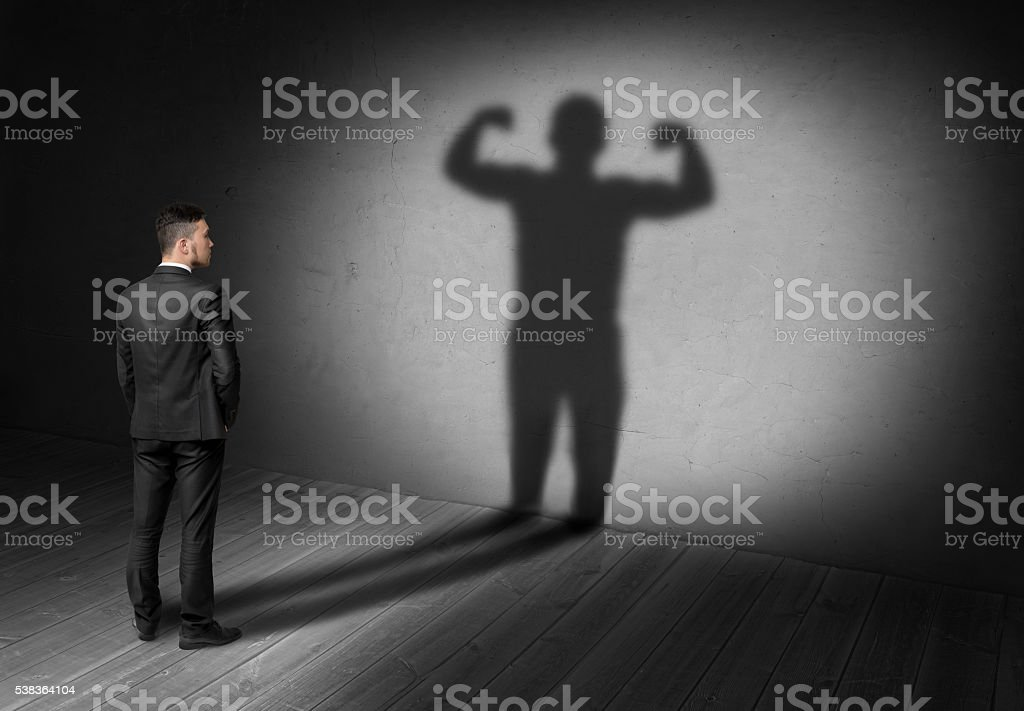 Back view of businessman looks to shadow with strong his stock photo