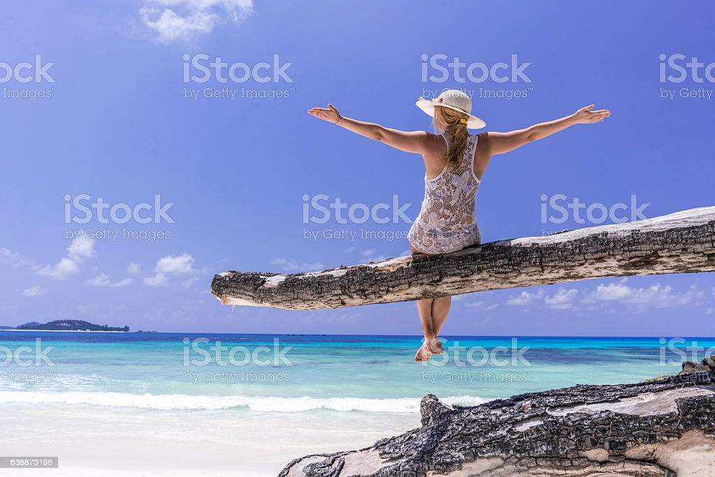 Back view of carefree woman on tree trunk at beach. stock photo