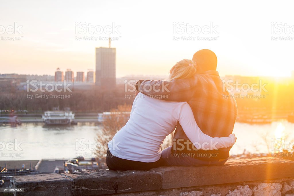 Back view of embraced couple enjoying a day at sunset. stock photo