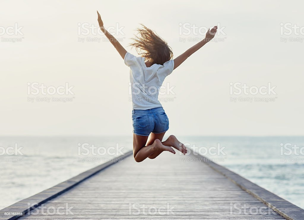 Back view of jumping girl on the pier stock photo