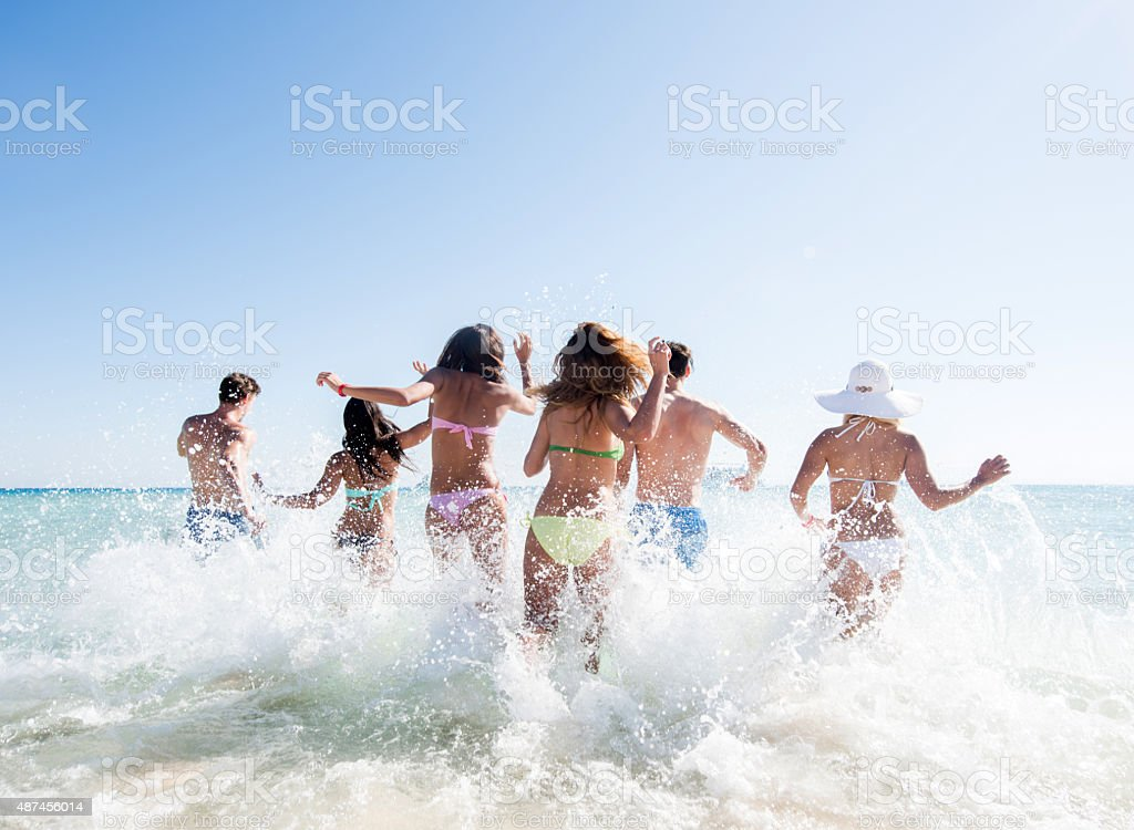 Back view of large group of friends running into sea. stock photo