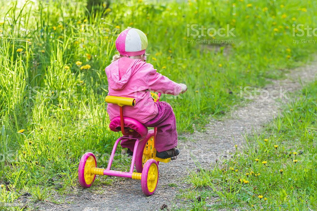 Back view of little girl riding pink and yellow tricycle stock photo