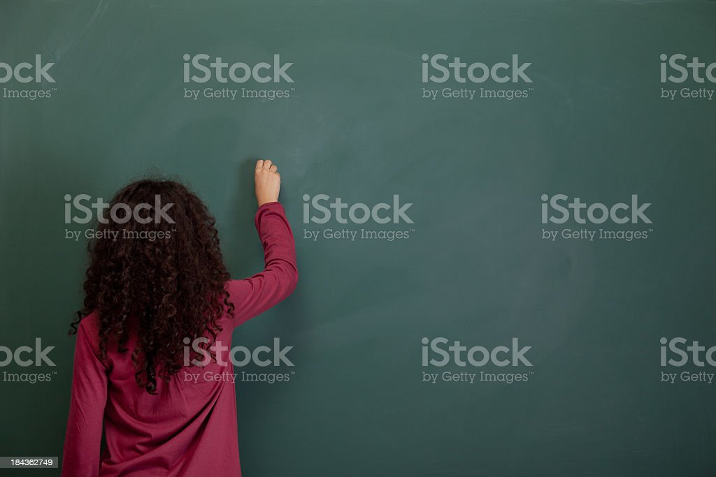 Back View Of Little Girl Writing On Blank Blackboard stock photo