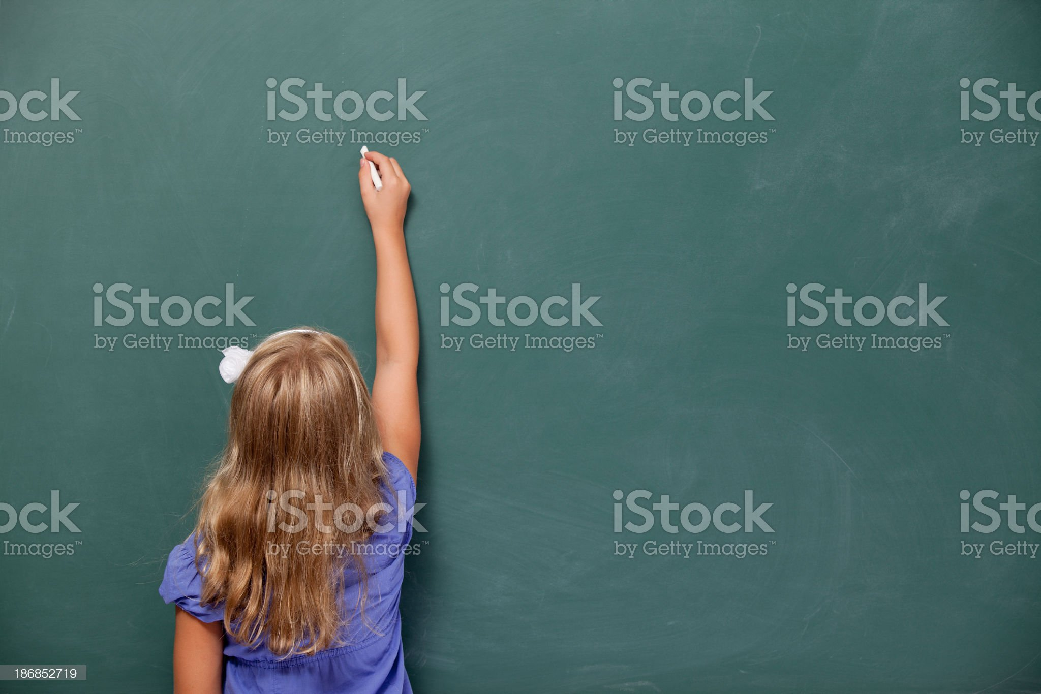 Back view Of Little Girl Writing On Blank Blackboard royalty-free stock photo