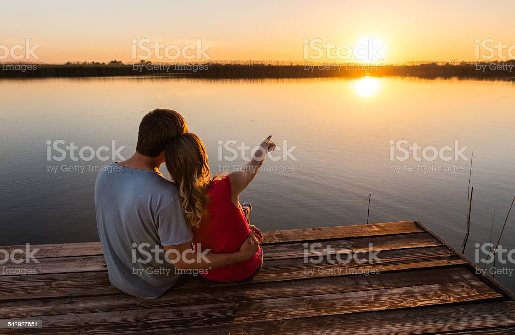 Back view of loving couple on a pier at sunset. stock photo