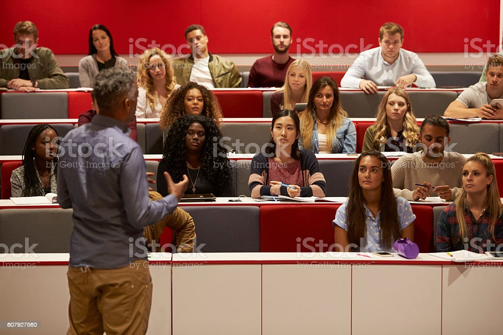 Back view of man presenting to students at a lecture stock photo