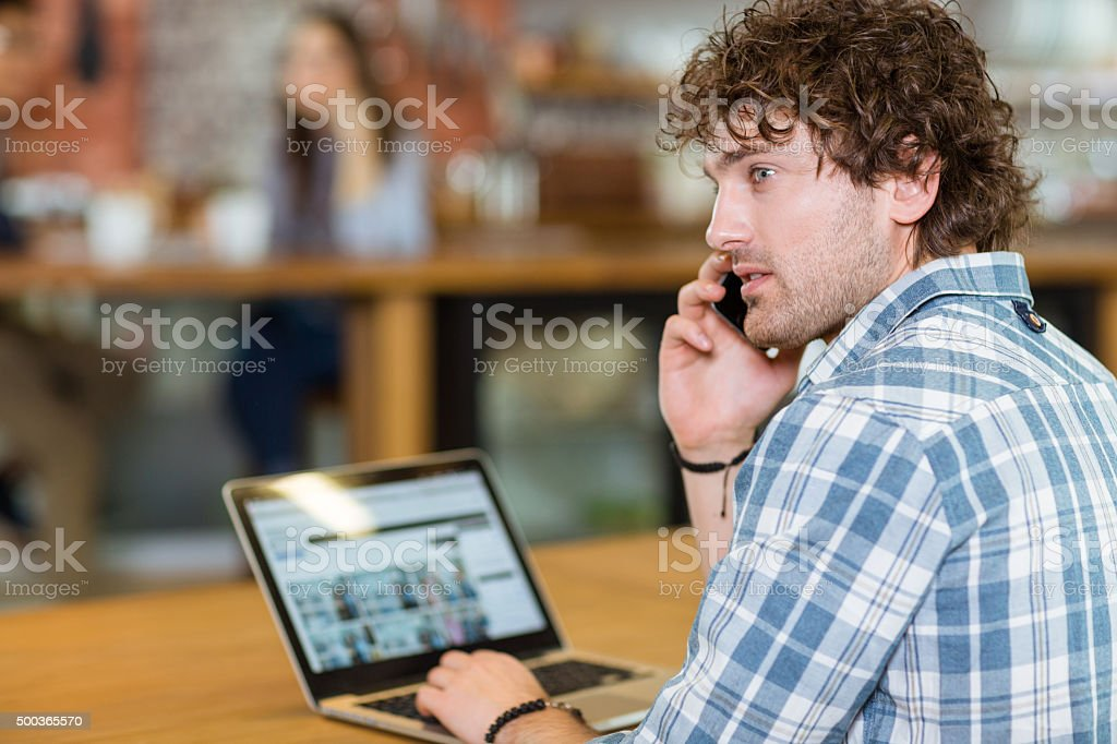 Back view of man using laptope and smartphone stock photo