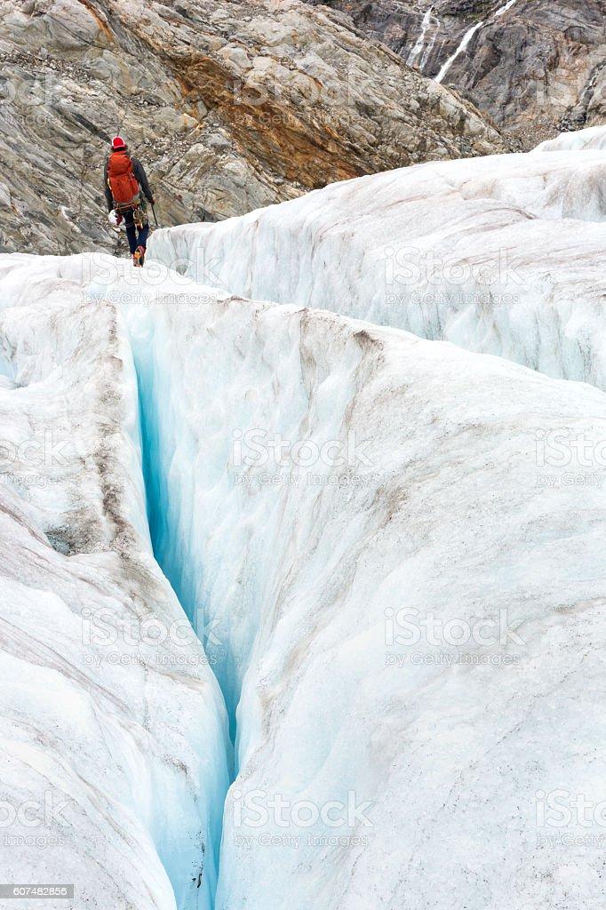 Back view of man walking between crevasses stock photo