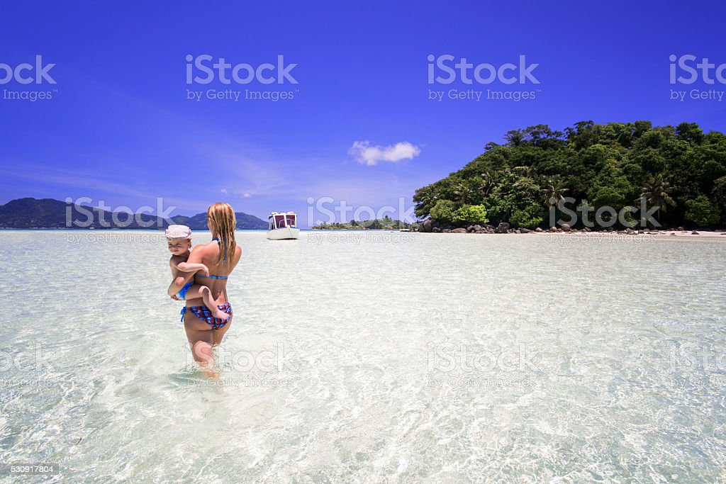 Back view of mother walking through sea with her son. stock photo